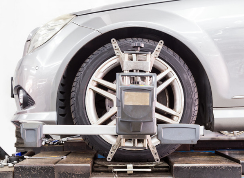 Photo of an alignment machine clamped to tire